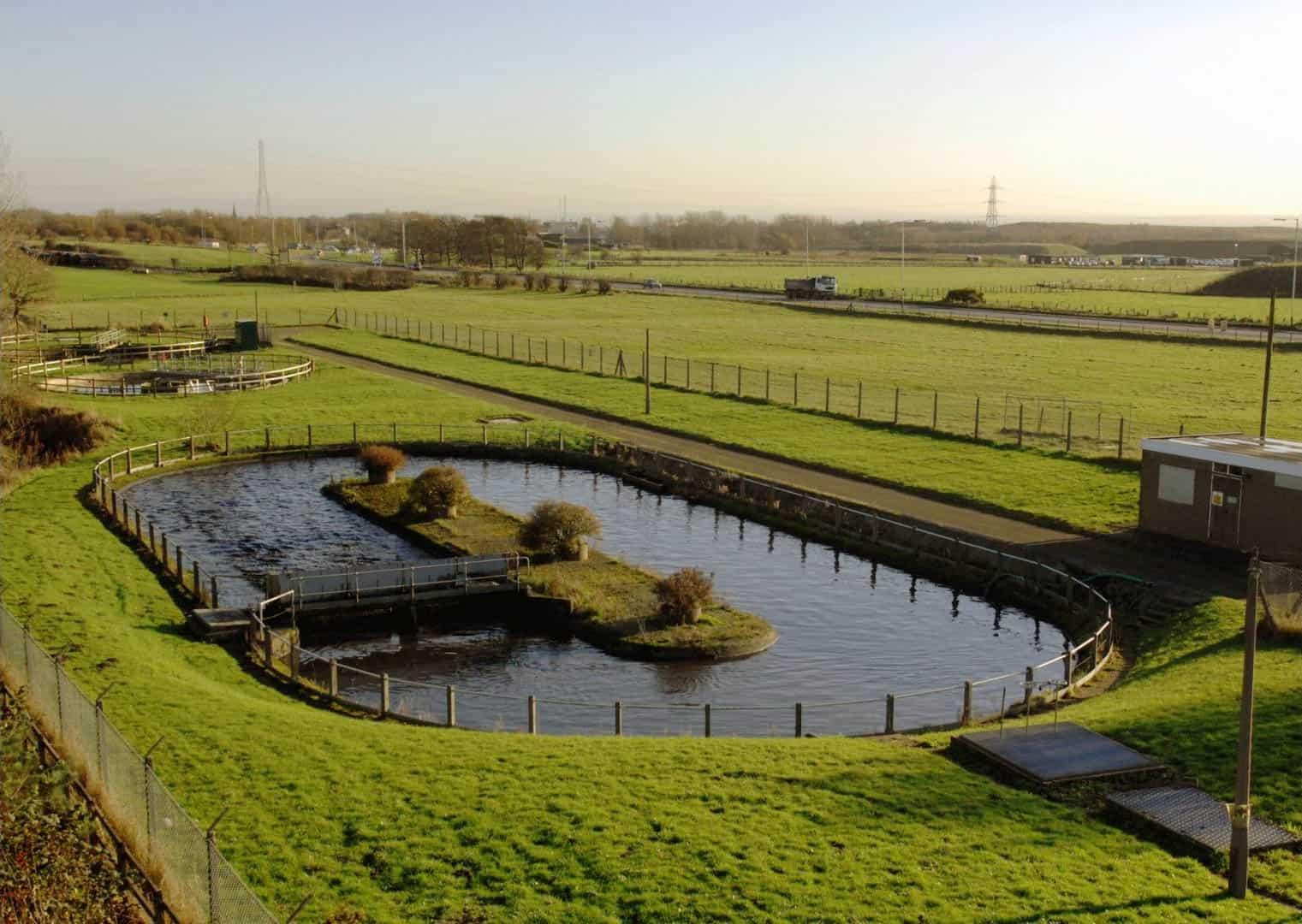 Industrielle Kläranlage umgeben von Feldern, die Grundwasser Monitoring betreibt.