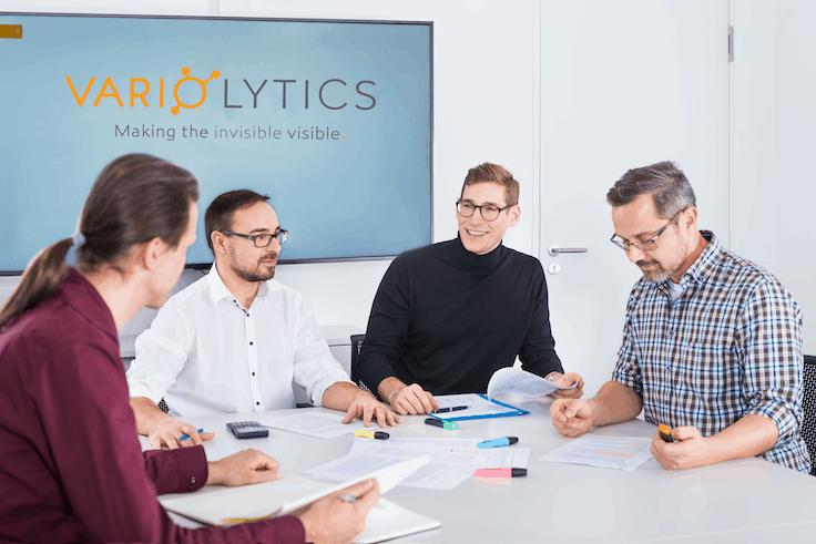 Das Gründerteam von Variolytics sitzt zusammen am Tisch.
