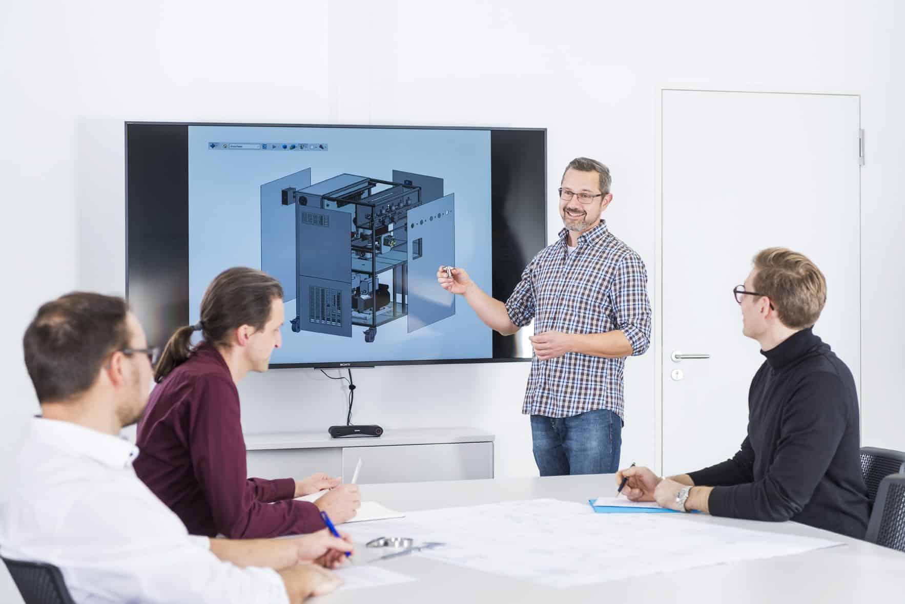 Ein Team-Mitglied hält eine Präsentation vor drei weiteren Personen